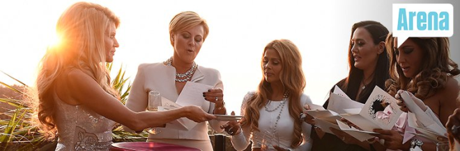 The other housewives gather around as Gamble hands out her wedding invitations