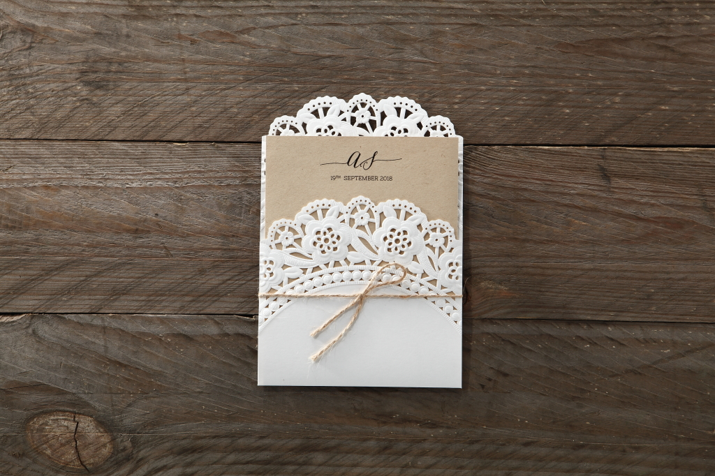 Intricate lace laser cut detailing on rustic invitation