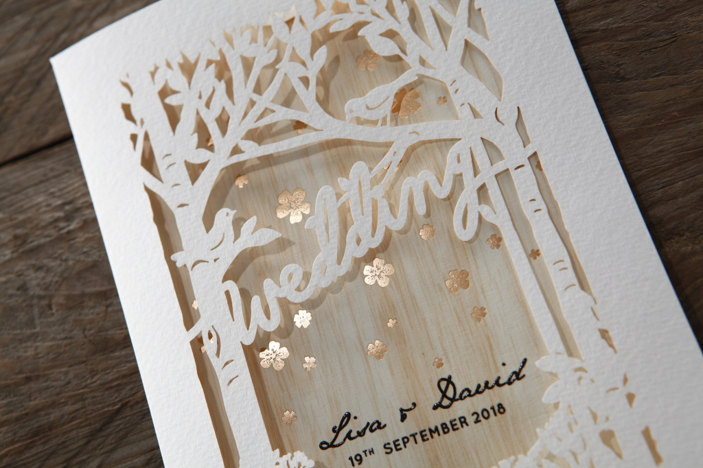 A forest inspired wedding invitation with golden flowers