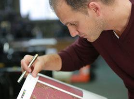 Adorn Invitation graphic designer checking a proof in a print shop.