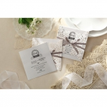 A pair of matte laser cut invitations with flower theme, one showing the square invite card out of its pocket