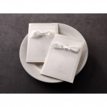 Classic invitation in white featuring satin ribbon, letterpress and crystal