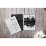 Two wedding invitations with one out of the black lace themed sleeve and one inside the pocket