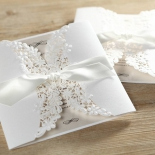 Unsealed white sleeved traditional invitation with flower designs.