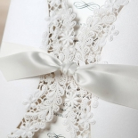 White sleeved die cut invitation featuring white ribbon