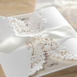 White ribbon wrapped matte bridal invite with flowers