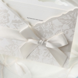 Bow accented traditional invite with floral designs in silk screen