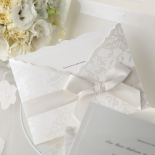 White themed flower bridal invite featuring white bow