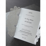 Embossed printed invitation card attached to a gated laser cut invite