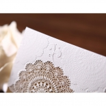 The flower embossing on the white matte paper up close
