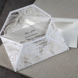 White modern invitation wrap featuring laser cut feather patterns
