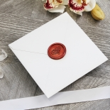 A square envelope opening with the inner layer showing black elegant text