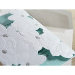 Flower designed white laser cut pocket with foil accents and blue insert